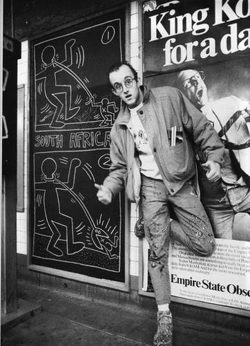 Keith Haring standing beside one of his subway drawings.