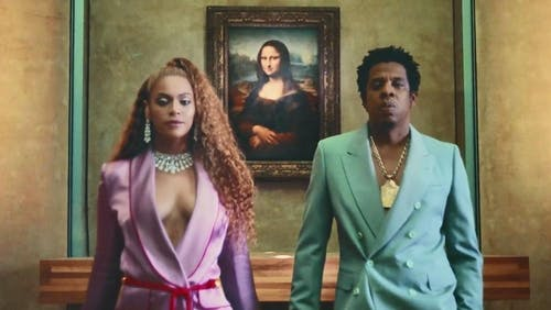 Jay-Z and Bejoncé stand in front of the Mona Lisa at the Louvre