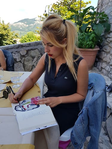 Claudia Marchetti drawing on a sunny terrace.