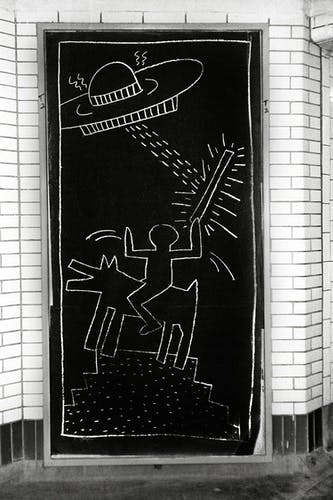 One of Keith Haring's subway drawings featuring some of his most popular subjects: ufo's and a dog.
