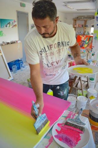 Alex Voinea at work in his colorful studio.