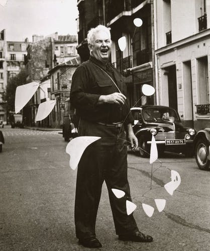 Calder on the street with his work 21 feuilles blanches (1953), Paris, 1954.