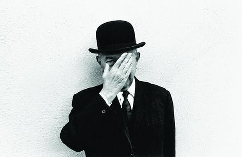 René Magritte, wearing a bowler hat, covering his face with his hand.