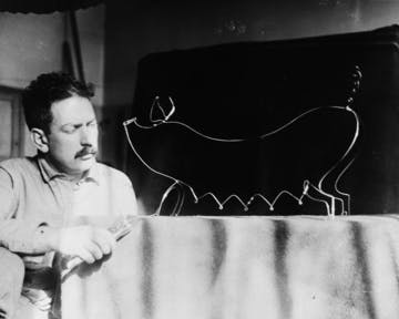 Alexander Calder with a metal wire creation depicting a sow.
