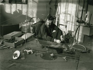 Alexander Calder sits on the floor in his studio with Cirque Calder (1926–31), 1929  Photograph by André Kertesz.