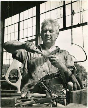 Alexander Calder at work, creating wire sculptures in his studio.