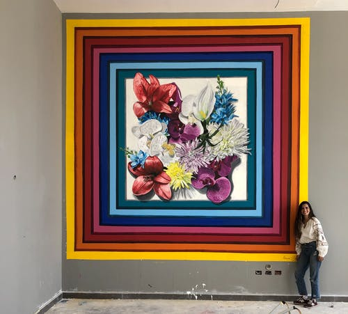 Artist Nourine Hammad poses in front of a big mura piece.