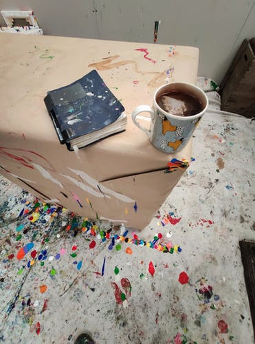 A journal and a cup of tea inside the studio of Derick Smith.
