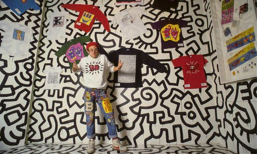 Keith Haring stands in front of his black and white mural showing of his merchandise in the Pop Shop.