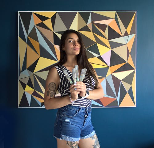 Malwina Puszcz poses in front of one of her newest paintings.