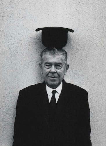 René Magritte wearing a bowler hat upside down atop his head.