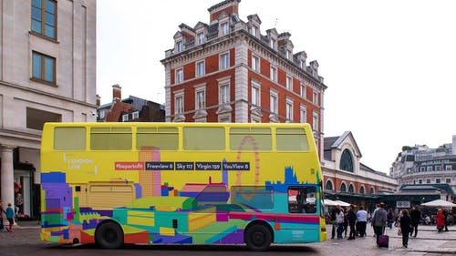 A bright and colourful London Bus with the Yoni ALter's city scape.