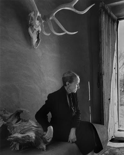 Georgia O'keeffe in her home with an animal skull on the wall.
